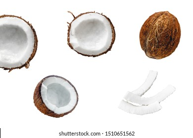 Whole coconut and chopped into chunks and chips on a light white wooden background. Top view
