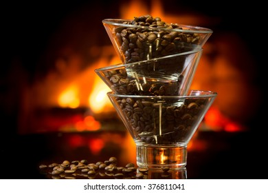 whole coffee beans in glass bowls with fire of fireplace on background