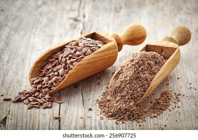whole and crushed flax seeds on old wooden table