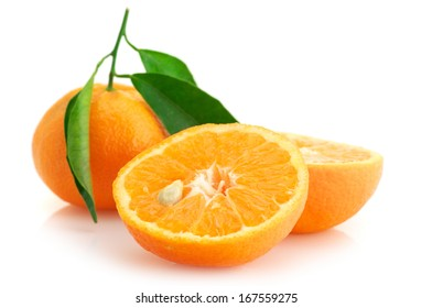 Whole and cut fresh tangerines with leaves isolated on white background.