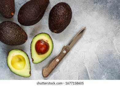Whole and cut ripe organic avocados and a knife on a grey  background. The Haas Avocado. Source of vitamins , trace elements , beta-carotene and omega-3 fatty acids . Healthy food, diet. copy space