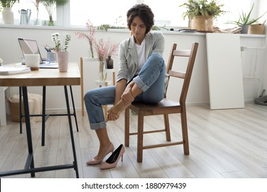 Whole day on stilettos. Tired young female florist decorator sitting on chair at work table taking off high heel shoe. Fatigued lady manager of craft store flower shop massaging bare foot feeling pain