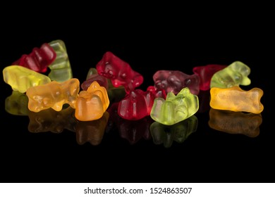 Lot of whole disordered gummy bear isolated on black glass