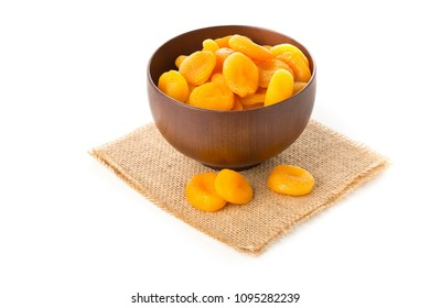 Whole dried apricots fruit in wooden bowl over white background