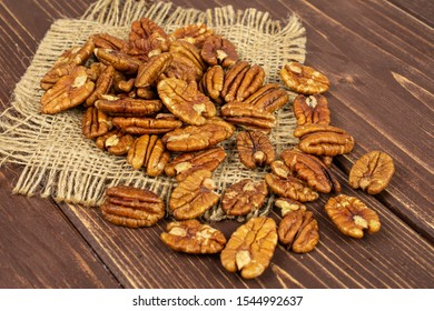 Lot of whole dry brown pecan nut on natural sackcloth on brown wood