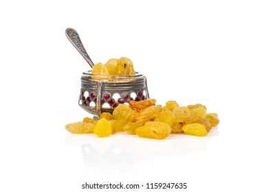 Lot of whole dry golden raisins sultana variety in small caviar bowl isolated on white background