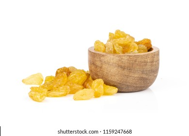 Lot of whole dry golden raisins sultana variety with wooden bowl isolated on white background