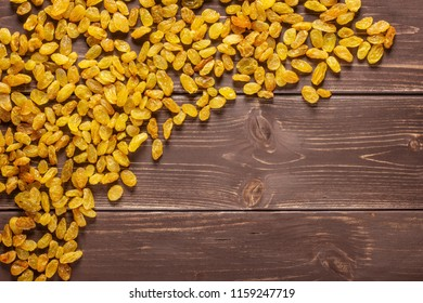 Lot of whole dry golden raisins sultana variety left upper corner flatlay on brown wood