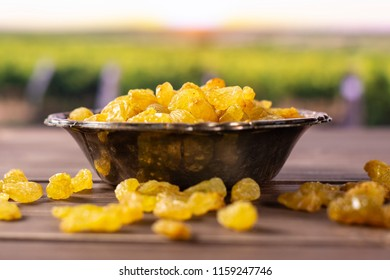 Lot of whole dry golden raisins sultana variety in old iron bowl with vineyard in background