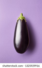 Whole eggplant on a purple background viewed from above. Top view of an aubergine. Copy space