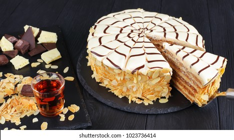 whole esterhazy torte and a slice of cake on spatula. cognac in a glass and ingredients on slate cutting board, authentic recipe, hungarian and austrian dessert, view from above, close-up