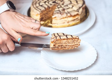 whole esterhazy torte and a slice of cake on knife. Woman's hands hold it. authentic recipe, hungarian and austrian dessert, view from above, close-up