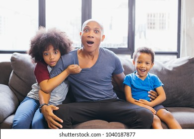 Whole family of African American watching and staring horror movie on TV at home. They are getting frightened and scared