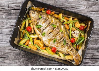 whole fish baked in a baking dish with potatoes, cherry tomatoes, green beans, lemon, baby carrots and basil on an old table, top view, horizontal