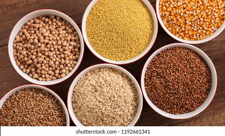 Whole foods diet base - various seeds in bowlson brown table, foundation for healthy life - top view, close-up