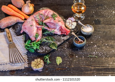 Whole Forest wild rabbit, Recipe with apple pie, Raw meat with spices and vegetables, Sea salt, red, white pepper and coriander in clay pots on an old black rustic table. magazine cover, copy space