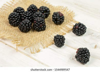 Lot of whole fresh black blackberry on natural sackcloth on white wood