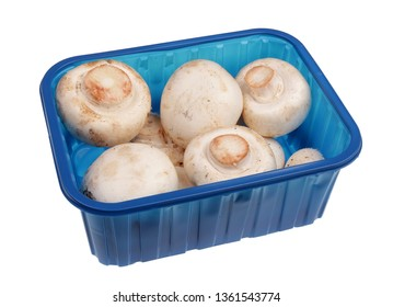 Whole fresh champignon mushrooms in blue plastic container. Isolated on white studio macro