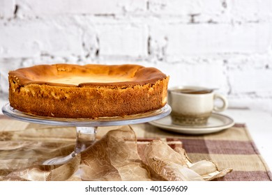 Whole fresh creamy traditional cheesecake on a glass plate with cup of coffee on the white brick wall