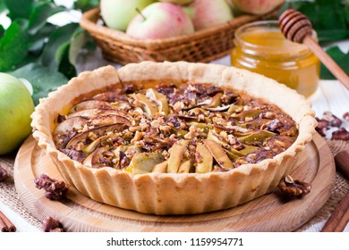 Whole fresh homemade apple pie with nuts and cinnamon on a wooden table