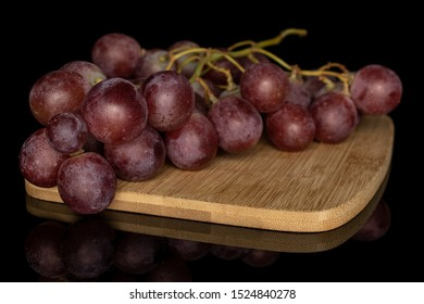 Lot of whole fresh purple grape rose on bamboo cutting board isolated on black glass