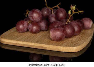 Lot of whole fresh purple grape rose cluster on bamboo cutting board isolated on black glass