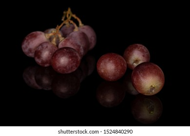 Lot of whole fresh purple grape rose front focus isolated on black glass
