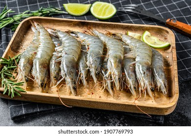 Whole fresh raw tiger prawns, shrimp on a wooden tray. Black background. Top view
