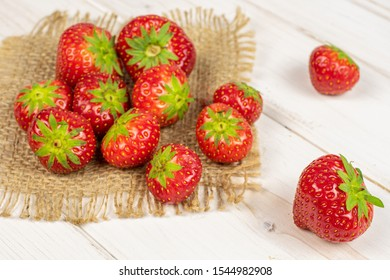 Lot of whole fresh red strawberry on natural sackcloth on white wood