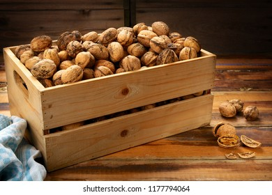 Whole fresh walnuts in wooden crate on an old table