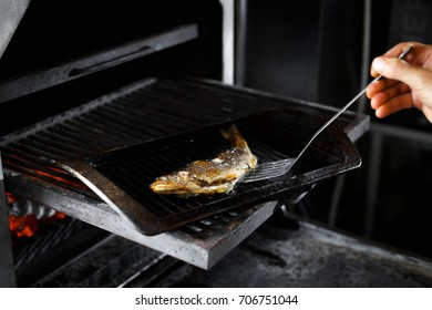 Whole freshwater trout roasting on a frying pan in a grill oven
