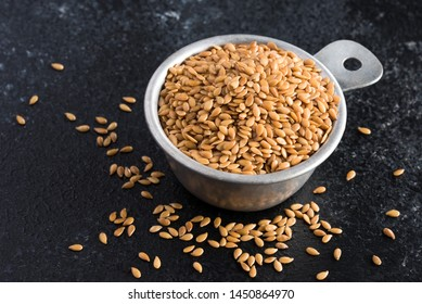 Whole Gold Flaxseeds Spilled from a Measuring Cup