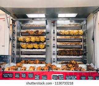 whole golden brown chickens on grill for sale on market in french town of besancon