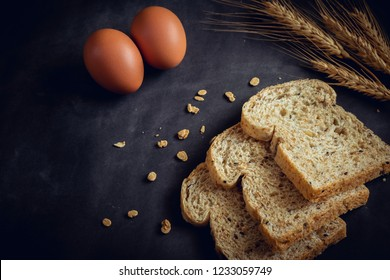 Whole grain bread and egg on dark background