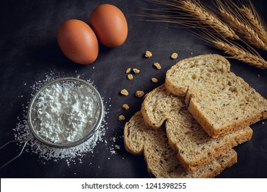 Whole grain bread, flour and egg on dark background
