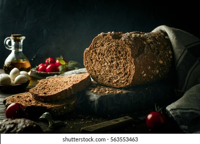 Whole grain bread on wooden cutting board with olive oil, tomato and basil . Dark toned photo with copy space.