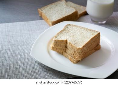 Whole Grain Bread in white dish and milk in glass on concrete table.