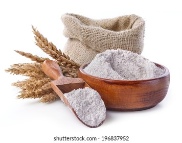 whole grain flour in a bowl and linen bag with a wooden spatula