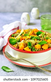 Whole grain fusilli pasta with pumpkin and pesto sauce in a white bowl on a light slate, stone or concrete background.