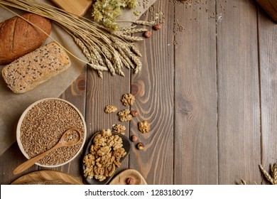 Whole grain, whole loaf and sliced pieces of multigrain bread contains whole grains (poppy, millet, flaxseed, pumpkin seeds, and sunflower seeds) isolated on dark wooden table with a copyspace.