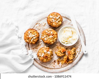 Whole grain muffins with dried apricots, oatmeal, apple, carrots and nuts on rustic cutting board on light background, top view. Healthy vegetarian food, dairy free