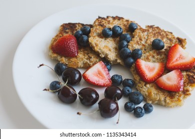 Whole grain pancake with cherry, strawberry and blueberry served on white plate. Healthy breakfast