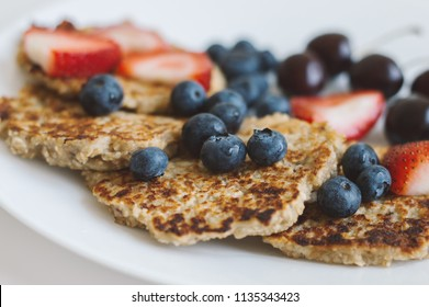 Whole grain pancakes from oat served with fresh blueberry, strawberry and cherry on white plate. Healthy eating