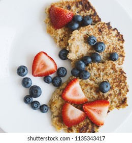 Whole grain pancakes with strawberry and blueberry on white plate. Oat pancakes with no added sugar. Healthy breakfast meal