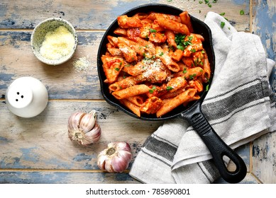 Whole grain pasta with chicken fillet in tomato sauce in a skillet over old rustic wooden background .Top view.