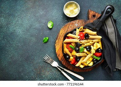 Whole grain pasta with tomato cherry, black olives and chicken in a skillet over dark slate,stone or concrete background.Top view with copy space.