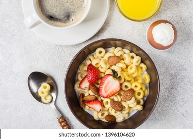 Whole grain rings cheerios with strawberry, coffee and egg. Balanced traditional breakfast.