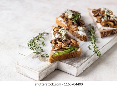 Whole grain rye bread toast with cream cheese or ricotta, mushroom and thyme on a white wooden cutting board.