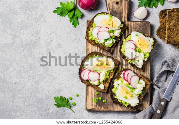 Whole grain toasted bread with smashed avocado radish eggs on cutting board. Top view, space for text.