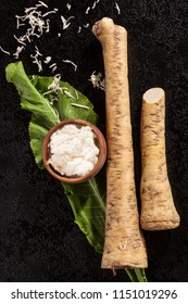 Whole and grated horseradish with leaves on black background from above. Healthy vegetable.